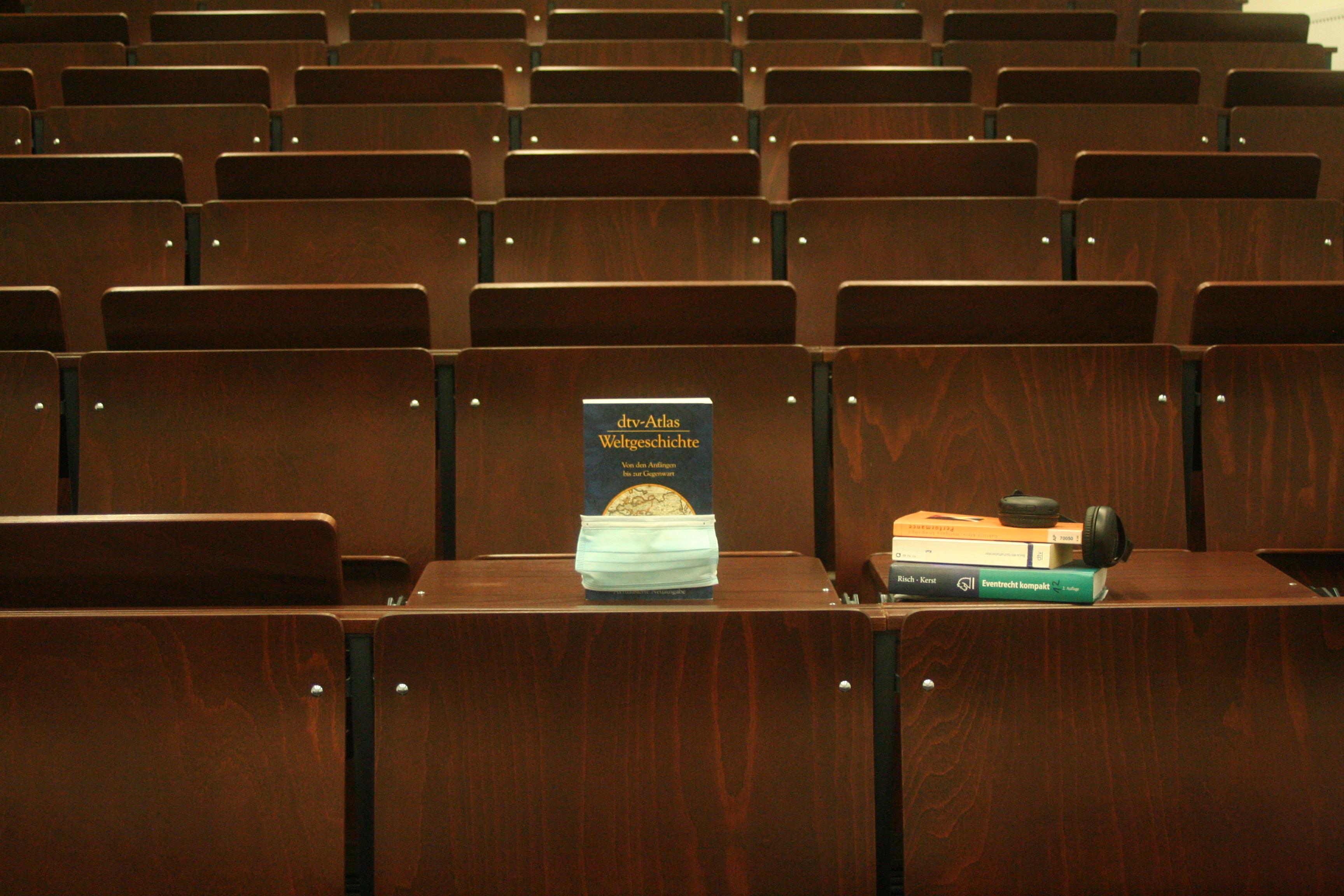 Hörsaal mit Büchern und Maske auf dem Tisch