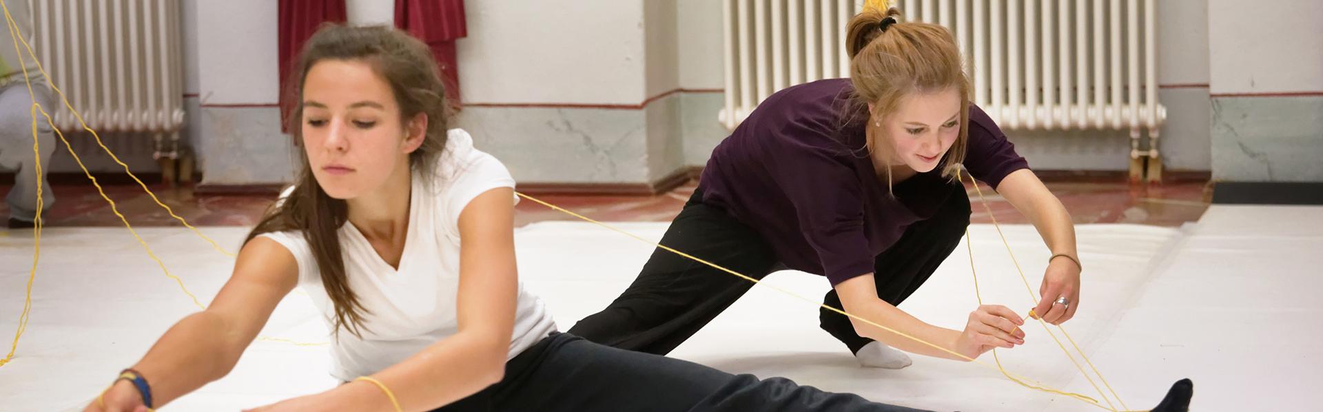 Bachelor-Studium Kultur und Management: Zwei Studentinnen bei Tanzdarstellung mit Wollfaden.
