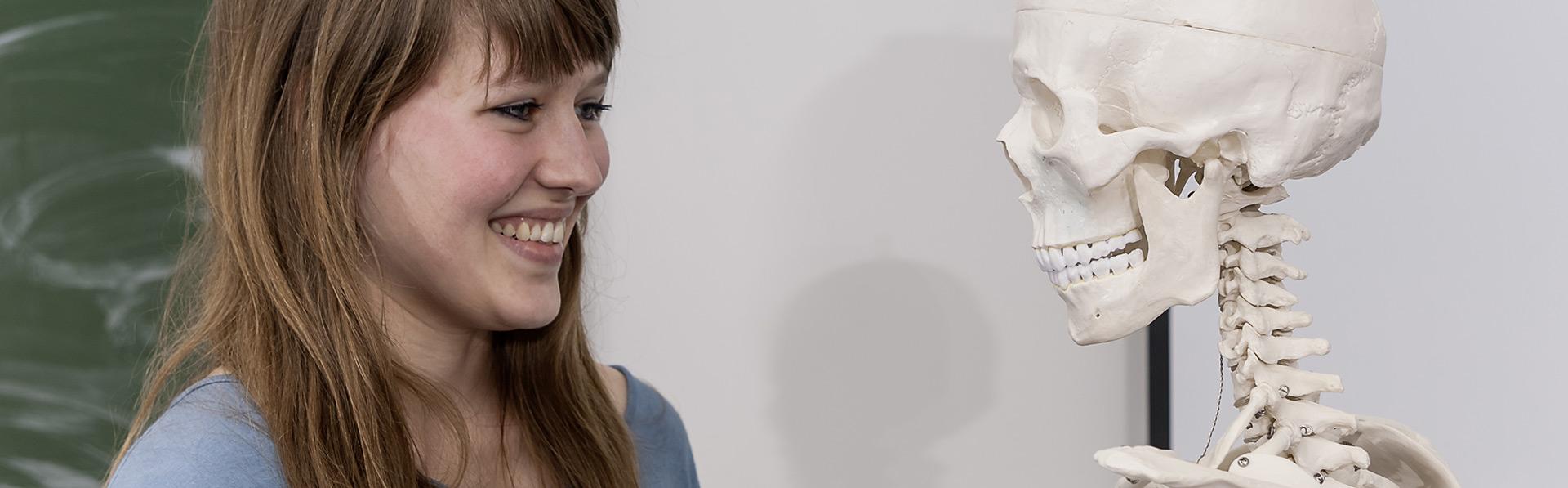 Bachelor Management im Gesundheitswesen: Studentin schaut Skelett in die Augen