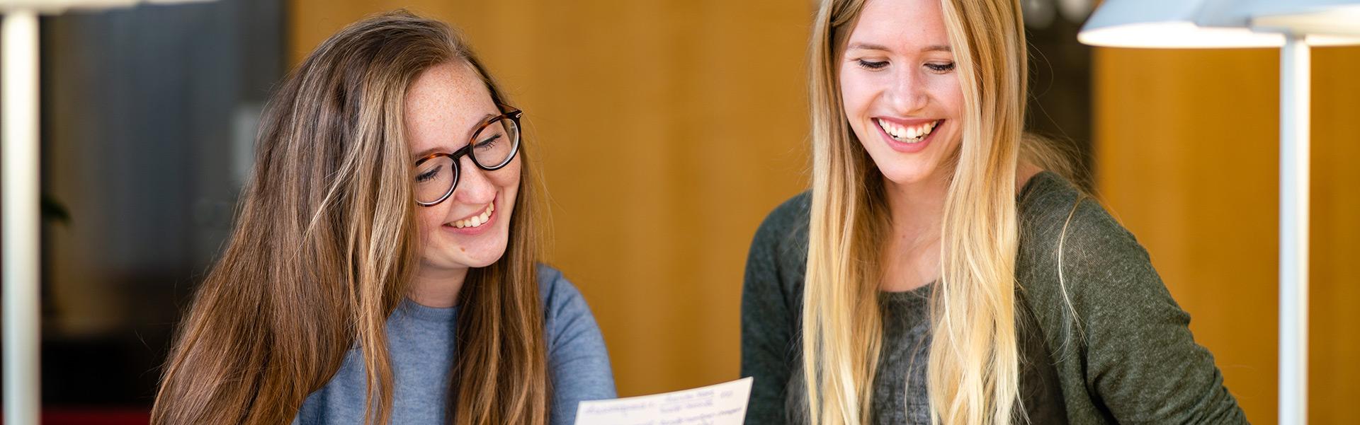 Bachelor-Studium Wirtschaft und Sprachen: Zwei lachende Studentinnen lesen etwas ab.