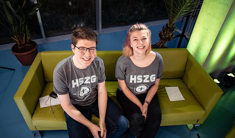 Cornelius Baier und Carolin Renner sitzen auf dem grünen Moderationssofa und schauen glücklich nach oben in die Kamera